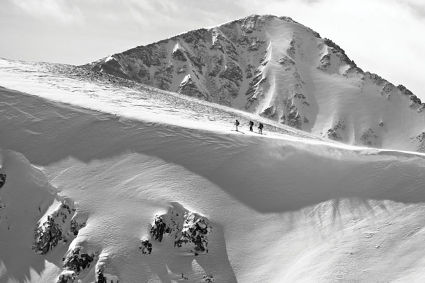 The Land Beyond: Crystal Peak looms in the background as skiers traverse Peak 6 into the more committing lines of the Inside Corner and North Chute in the Breckenridge backcountry.