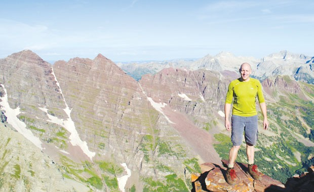 guy in the sky: Bart Deferme standing atop 14,025-foot pyramid peak in front of the maroon bells.