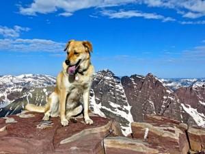 Sophie sitting next to the summit marker on Pyramid Peak